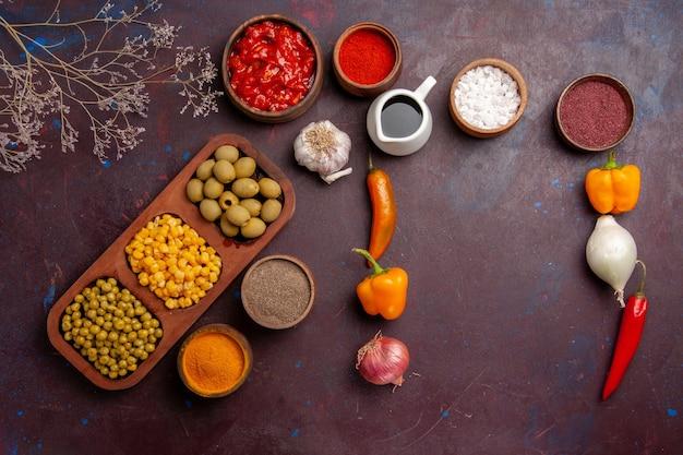 暗い空間に野菜を使ったさまざまな調味料の上面図
