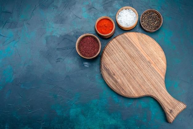 木製の机でさまざまな調味料の上面図。紺色の背景に。