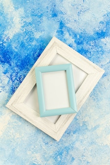 Top view different sizes blank picture frames on blue white grunge