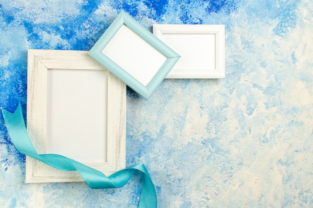 Top view different sizes empty photo frames blue ribbon on blue white grunge with copy place