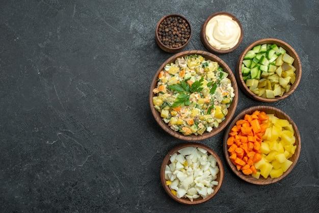 Вид сверху различных нарезанных овощей на темной поверхности еды закуска овощной салат
