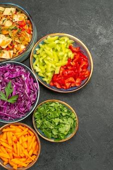 Вид сверху на разные нарезанные овощи с куриным салатом на темном полу, здоровый салат, диета