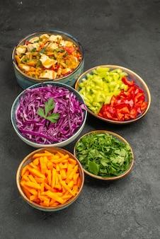 Вид сверху различных нарезанных овощей с куриным салатом на сером столе салат для здоровья диеты