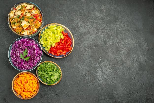 Vista dall'alto diverse verdure a fette con verdure sull'insalata di dieta salutare tavolo scuro