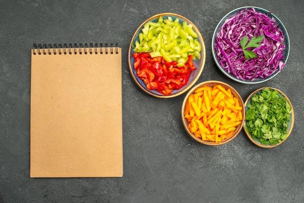 Вид сверху на разные нарезанные овощи с зеленью на темном столе, здоровая диета