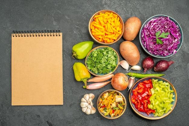 Вид сверху на разные нарезанные овощи с зеленью на темном столе, диетическое питание