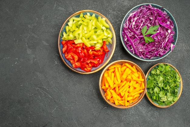 Вид сверху разные нарезанные овощи с зеленью на темном столе, салат, здоровая диета