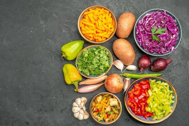Вид сверху различных нарезанных овощей с зеленью на темном столе, салат, еда, здоровая диета