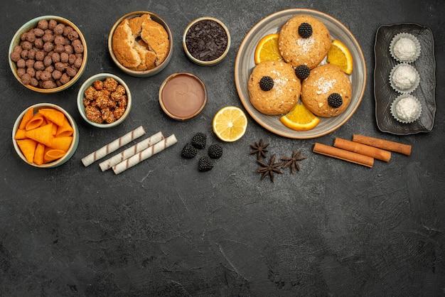上面図さまざまなスナックcipsクッキーフレークとナッツ灰色の表面の食事スナック朝食の色