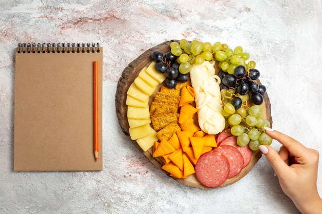 上面図さまざまなスナックcipsソーセージチーズと白いスペースに新鮮なブドウ