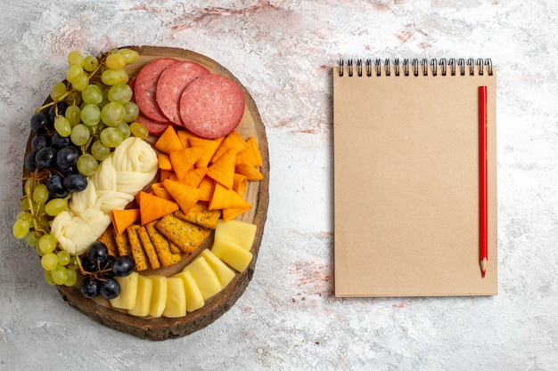 Top view different snacks cips sausages cheese and fresh grapes on light white space