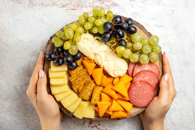 Top view different snacks cips sausages cheese and fresh grapes on white space