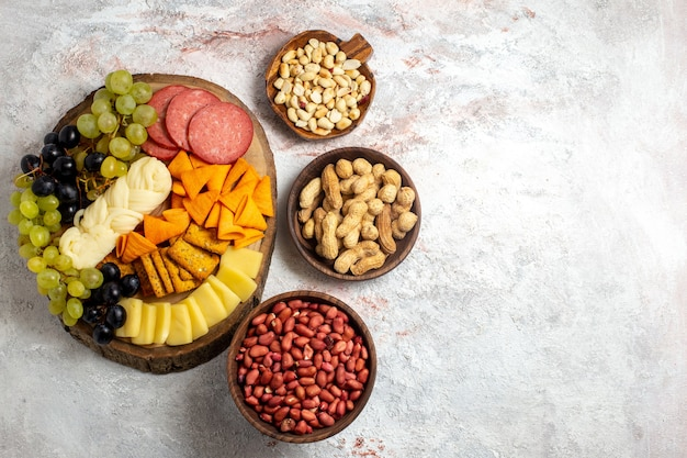 Top view different snacks cips sausages cheese and fresh grapes with nuts on white space