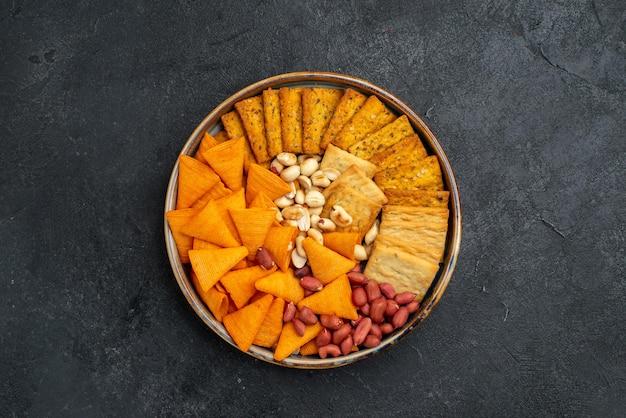 Вид сверху разные закуски, крекеры, орехи и чипсы на темно-серой поверхности