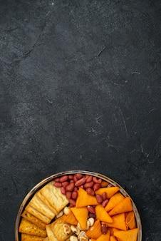 Vista dall'alto diversi snack cracker noci e patatine sulla scrivania grigio scuro