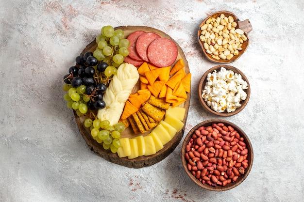 Vista dall'alto diversi snack uva fresca formaggio cips con noci su uno spazio bianco