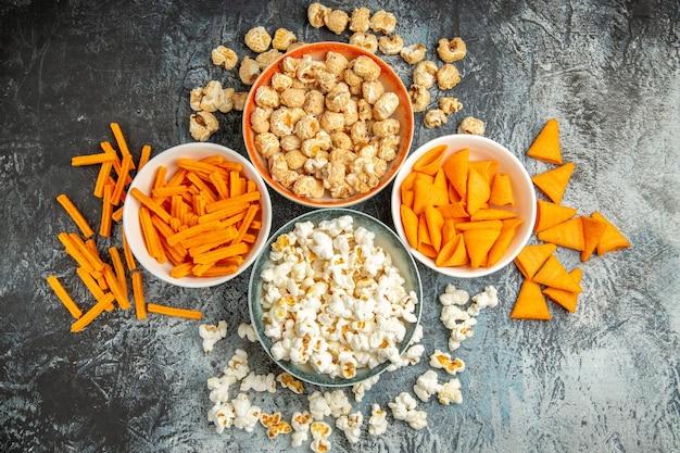 Vista dall'alto diversi snack per l'ora del film su una superficie chiara-scura