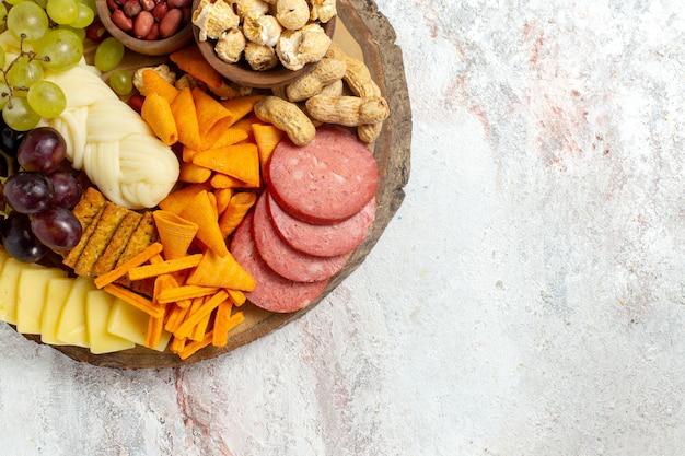 Vista dall'alto diversi snack noci cips formaggio e salsicce su sfondo bianco dado spuntino pasto cibo