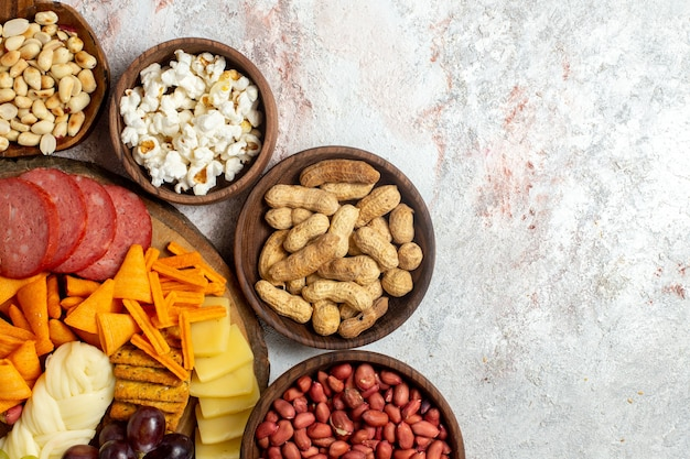 Top view different snacks nuts cips cheese and sausages on white background nut snack meal food