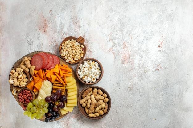 Вид сверху разные закуски, орехи, чипсы, виноград, сыр и колбасы на светлом белом фоне, ореховая закуска, еда, фрукты