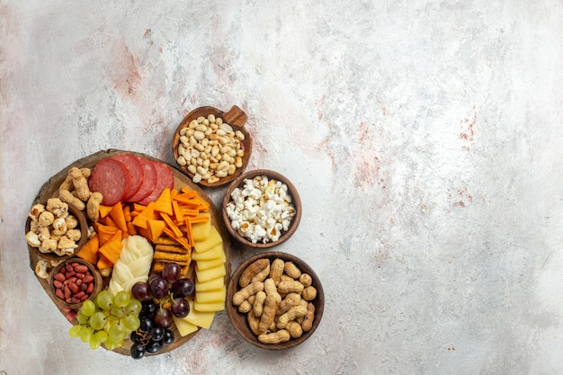 Top view different snacks nuts cips grapes cheese and sausages on a light white background nut snack meal food fruit