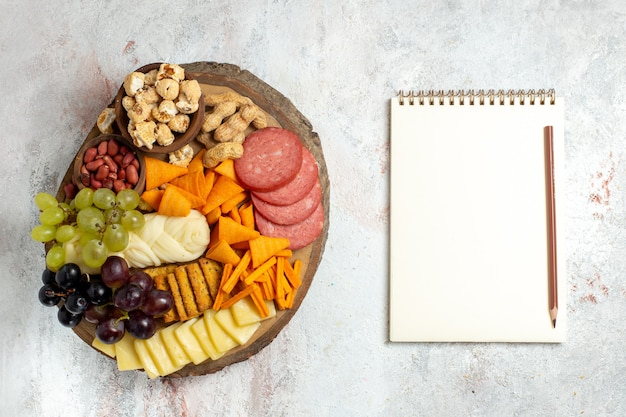 Top view different snacks nuts cips grapes cheese and sausages on a white background nut snack meal food fruits