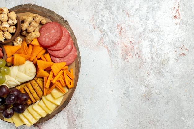 Vista dall'alto diversi snack noci cips uva formaggio e salsicce sulla scrivania bianca dado spuntino pasto cibo frutta