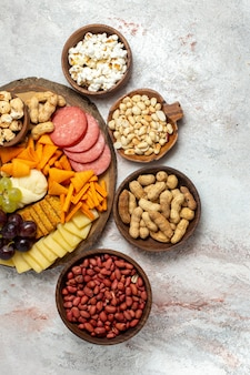 Top view different snacks nuts cips grapes cheese and sausages on white surface nuts snack meal food fruit