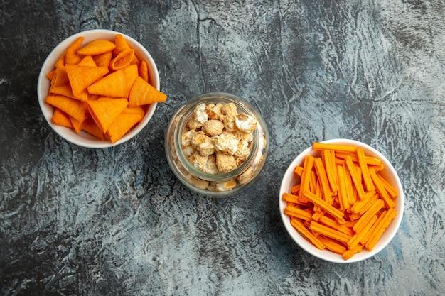 Vista dall'alto diversi snack popcorn fette biscottate e patatine sulla superficie scura