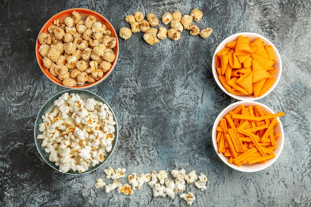 Vista dall'alto diversi snack popcorn fette biscottate e patatine sulla scrivania leggera
