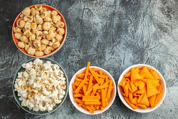 Vista dall'alto diversi snack popcorn fette biscottate e patatine sulla superficie chiara