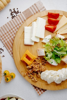 Top view of different sorts of cheese with nuts on a wooden plate