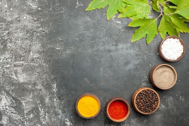 회색 배경에 작은 그릇 소금 후추에 상위 뷰 다른 향신료