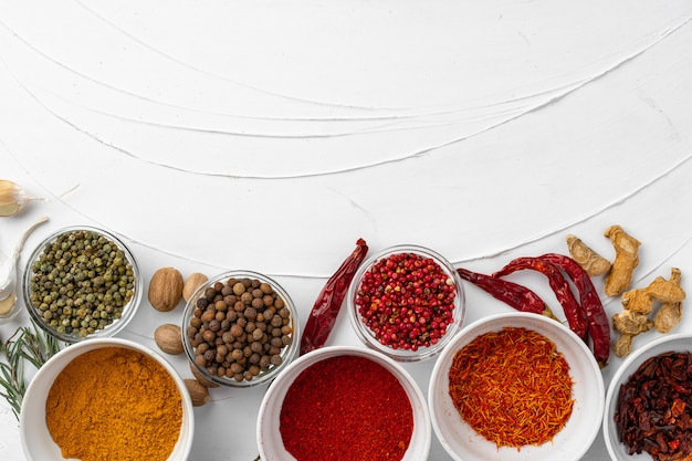 Top view of different spices on white textured background