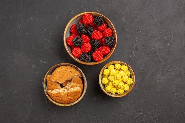 暗い背景の小さな鉢の中のさまざまな砂糖菓子の上面図砂糖菓子グッディボンボンカラーベリー