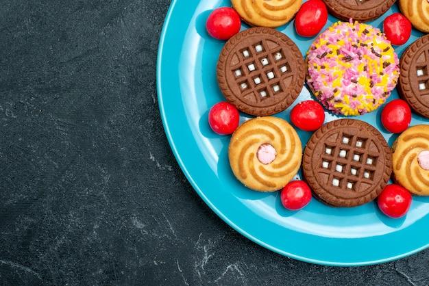 平面図灰色の表面にキャンディーが付いたプレート内のさまざまなシュガークッキーキャンディーシュガースウィートティークッキービスケット