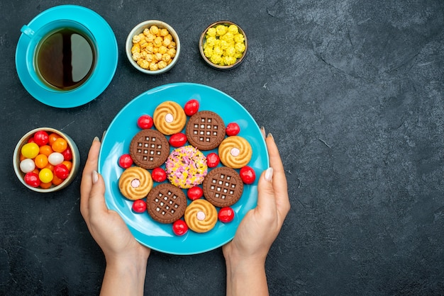 灰色の表面にキャンディーとお茶を入れたさまざまなシュガークッキーの上面図キャンディースウィートティークッキービスケットシュガー