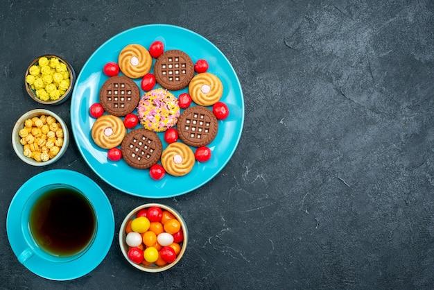 Vista dall'alto diversi biscotti di zucchero con caramelle e tazza di tè sul biscotto di biscotti di tè dolce zucchero candito scrivania grigia
