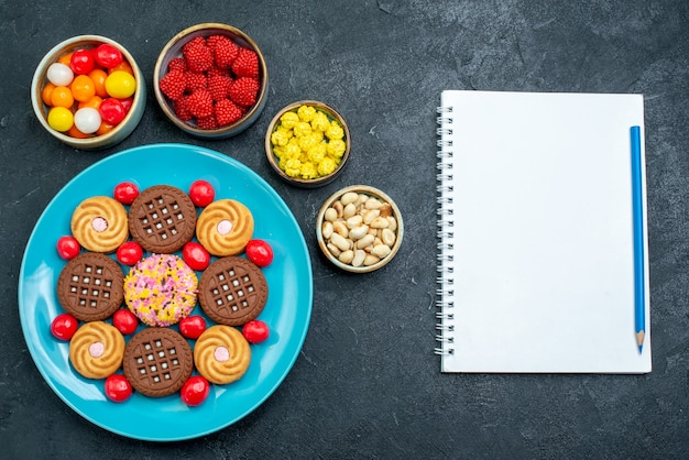 Vista dall'alto diversi biscotti di zucchero con le caramelle sui biscotti dolci del biscotto della caramella di zucchero di superficie grigia