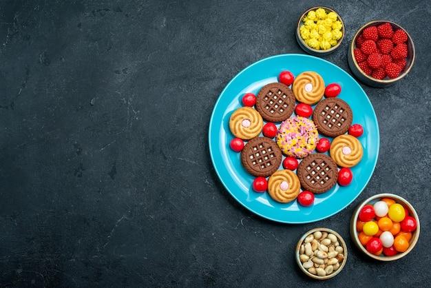 灰色の表面のプレートの内側にキャンディーが付いたさまざまなシュガークッキーの上面図キャンディースウィートティークッキービスケットシュガー