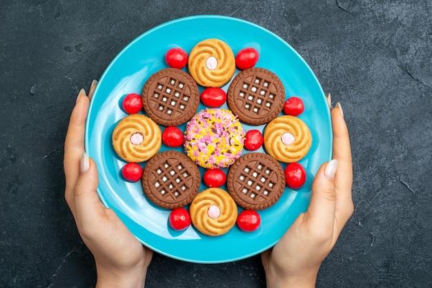 灰色の表面にキャンディーが付いたさまざまなシュガークッキーの上面図キャンディースウィートティークッキービスケットシュガー