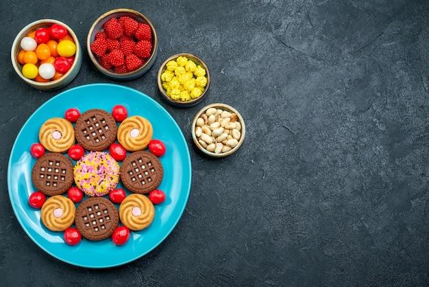 灰色の表面にキャンディーが付いたさまざまなシュガークッキーの上面図シュガーキャンディースイートビスケットクッキー