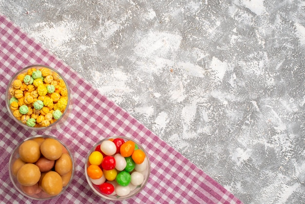 Top view of different sweet candies inside glasses on white surface