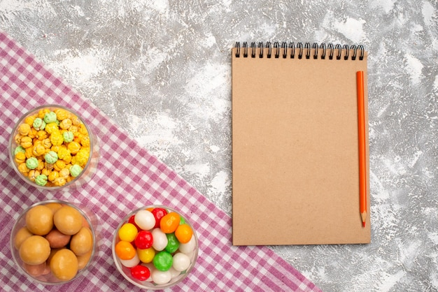 Top view of different sweet candies inside glasses with notepad on white surface