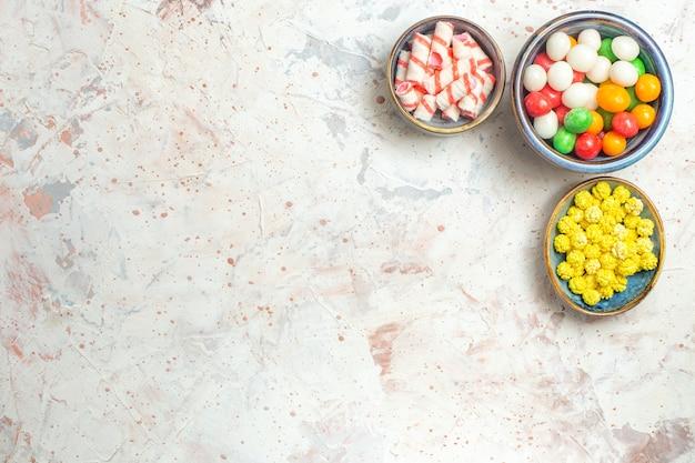 上面図白いテーブルの色のキャンディースイートにコンフィチュール付きのさまざまな甘いキャンディー