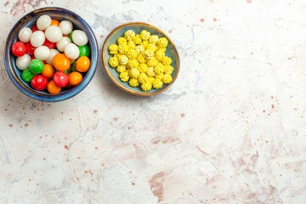 Vista dall'alto diverse caramelle dolci con confetture sul tavolo bianco color caramelle dolci