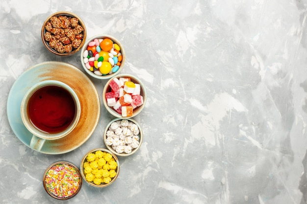 Top view of different sweet candies with marshmallows and tea on white surface