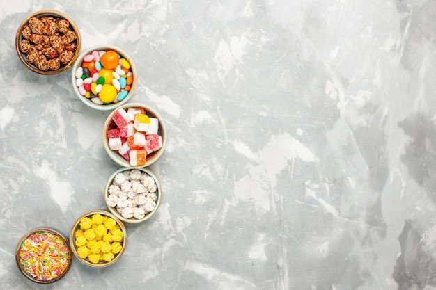 Top view of different sweet candies with marshmallows on white surface