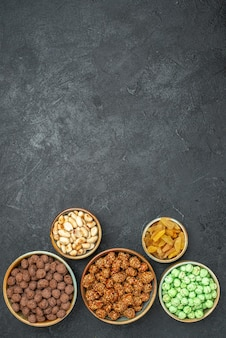 Top view of different sweet candies with nuts and raisins on grey