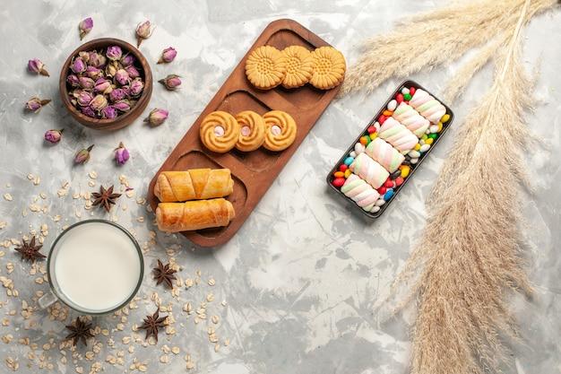 Вид сверху разные сладкие печенья с молоком и конфетами на белом фоне сахарные конфеты сладкий бисквитный пирог торт печенье
